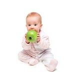 Nettes glückliches Baby isst den grünen lokalisierten Apfel der Frucht Lizenzfreie Stockfotos