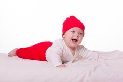Nettes glückliches Babymädchenkind, das im Bett liegt Stockfotos