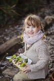 Nettes glückliches blondes Kindermädchen mit Eikasten mit Anlagen im Vorfrühlingsgarten Lizenzfreie Stockfotografie