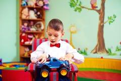 Nettes glückliches Kind auf Rollstuhl mit Geschenk im Kindergarten für Kinder mit speziellem Bedarf stockbild
