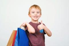 Nettes glückliches Kind mit bunten Einkaufstaschen auf weißem Hintergrund Stockbild