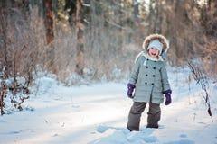 Nettes glückliches Kindermädchen auf dem Weg im sonnigen Wald des Winters Lizenzfreies Stockbild