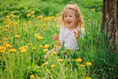 Nettes glückliches Kindermädchen auf Löwenzahnblumenfeld Stockfotografie
