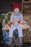 Nettes glückliches Kindermädchen beim Weihnachtshut- und -strickjackensitzen im Freien Stockfoto