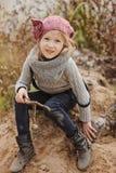 Nettes glückliches Kindermädchen, das auf der Flussseite im Herbst spielt Stockbilder