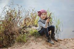Nettes glückliches Kindermädchen, das auf der Flussseite im Herbst spielt Lizenzfreies Stockfoto