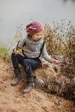 Nettes glückliches Kindermädchen, das auf der Flussseite im Herbst spielt Lizenzfreies Stockbild