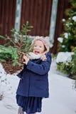 Nettes glückliches Kindermädchen, das im schneebedeckten Garten des Winters mit Korb von Tannenzweigen spielt Stockbild