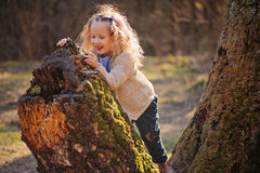 Nettes glückliches Kindermädchen, das mit altem Baum im Vorfrühlingswald spielt Stockbilder