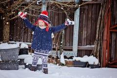 Nettes glückliches Kindermädchen, das Spaß hat und Schnee in Wintergarten wirft Stockfotos