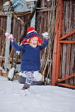 Nettes glückliches Kindermädchen, das Spaß hat und Schnee in Wintergarten wirft Stockfotografie