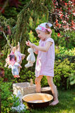 Nettes glückliches Kindermädchen, das Spielzeugwäsche im Sommergarten spielt und Spielzeug hängt Lizenzfreies Stockbild
