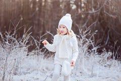 Nettes glückliches Kindermädchen in der weißen Ausstattung gehend in gefrorenen Winterwald Stockfotografie