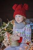 Nettes glückliches Kindermädchen im Weihnachtshut und Porträt der Strickjacke im im Freien Lizenzfreies Stockfoto