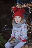 Nettes glückliches Kindermädchen im Weihnachtshut und Porträt der Strickjacke im im Freien Lizenzfreie Stockfotografie