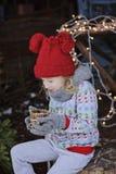 Nettes glückliches Kindermädchen im Weihnachtshut und -strickjacke mit hölzernem Kerzenhalter Stockfotografie