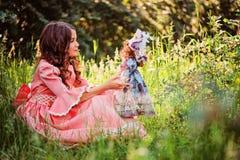 Nettes glückliches Kindermädchen in Märchenprinzessinkleid, das mit Puppe auf dem Weg im Sommer spielt Lizenzfreies Stockbild