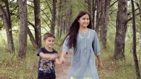 Nettes glückliches kleinen laufendes Händchenhaltenlächeln des Mädchens und des Jungen Bruder und Schwester sind zusammen für imm stock footage