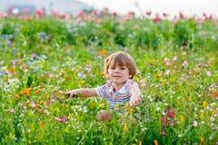 Nettes glückliches kleines blondes Kind auf dem blühenden Blumengebiet Stockbilder