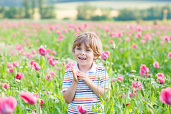 Nettes glückliches kleines blondes Kind in blühender Mohnblume Stockfotos