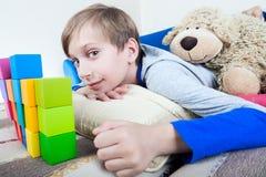 Nettes glückliches kleines Kind, das auf einem Sofa spielt mit bunten Würfeln liegt Stockfoto