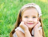 Nettes glückliches kleines Mädchen auf der Wiese Stockfotografie