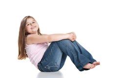 Nettes glückliches kleines Mädchen, das auf weißem Hintergrund sitzt lizenzfreie stockbilder