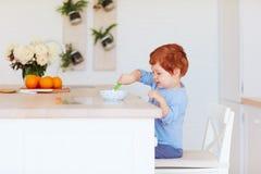 Nettes glückliches Kleinkindbaby, das morgens am Tisch, frühstückend sitzt lizenzfreies stockfoto