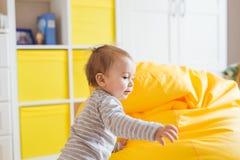 Nettes glückliches lachendes Baby, das auf weißem Schlafzimmer spielt lizenzfreie stockbilder