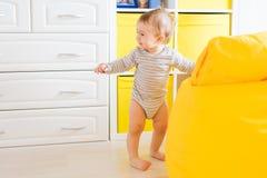 Nettes glückliches lachendes Baby, das auf weißem Schlafzimmer spielt stockbild