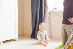 Nettes glückliches lachendes Baby, das auf weißem Schlafzimmer spielt stockbilder