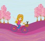 Nettes glückliches Mädchen, das ein Fahrrad reitet Stockbild