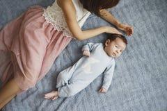 Nettes glückliches Mädchen, das ihren neugeborenen Babybruder hält Grauer Hintergrund Hübsches Baby in der blauen Kleidung lizenzfreies stockfoto