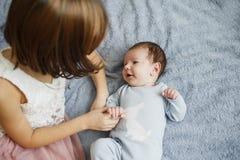 Nettes glückliches Mädchen, das ihren neugeborenen Babybruder hält Grauer Hintergrund Hübsches Baby in der blauen Kleidung stockbild