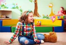 Nettes glückliches Mädchen, das im Kindergarten für Kinder mit speziellem Ne spielt lizenzfreies stockfoto