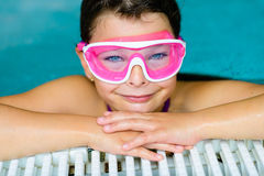 Nettes glückliches Mädchen in der rosa Schutzbrillenmaske im Swimmingpool Stockfoto