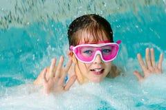 Nettes glückliches Mädchen in der rosa Schutzbrillenmaske im Swimmingpool Lizenzfreies Stockbild