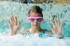 Nettes glückliches Mädchen in der rosa Schutzbrillenmaske im Swimmingpool Lizenzfreie Stockbilder