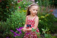 Nettes glückliches Mädchen in einem blühenden Garten Stockbild