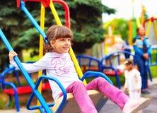 Nettes glückliches Mädchen, Kind, das Spaß auf Schwingen am Spielplatz hat Stockfoto