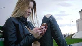 Nettes glückliches Mädchen mit dem langen blonden Haar in der Lederjacke richtet das Gebrauchsgerät gerade, das auf der Bank, Nah Stockfotos