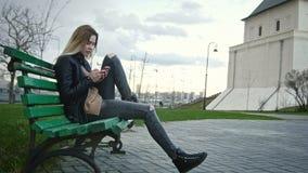 Nettes glückliches Mädchen mit dem langen blonden Haar in der Lederjacke richtet das Gebrauchsgerät gerade, das auf der Bank sitz Stockfoto
