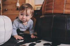 Nettes glückliches 11-monatiges Baby, das zu Hause, Lebensstilgefangennahme im gemütlichen Innenraum spielt Stockfotos