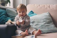 Nettes glückliches 11-monatiges Baby, das zu Hause, Lebensstilgefangennahme im gemütlichen Innenraum spielt Stockfoto