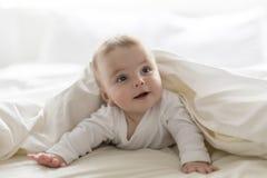 Nettes glückliches 7-monatiges Baby in der liegenden und spielenden Windel Lizenzfreies Stockfoto