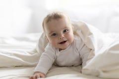 Nettes glückliches 7-monatiges Baby in der liegenden und spielenden Windel Lizenzfreie Stockfotos