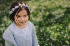 Nettes glückliches träumerisches Kleinkindkindermädchen, das in den blühenden Frühlingsgarten, Ostern feiernd im Freien geht Stockfoto
