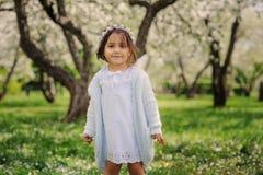 Nettes glückliches träumerisches Kleinkindkindermädchen, das in den blühenden Frühlingsgarten, Ostern feiernd im Freien geht Stockbild
