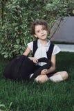 Nettes grundlegendes Schulmädchen in der Uniform, die mit Rucksack auf Gras sitzt Stockbilder
