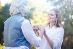 Nettes Händchenhalten der jungen Frau mit Großmutter im Park Stockbild